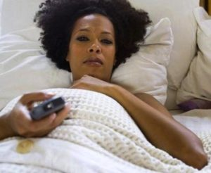 black-woman-in-bed-watching-tv